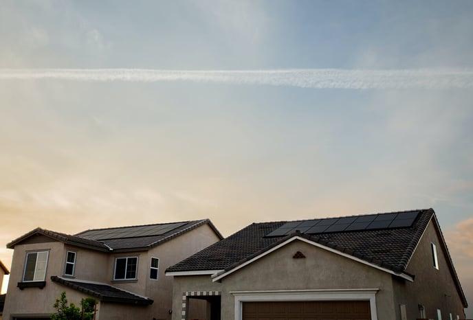 panneaux-solaires-toit-deux-maisons-ciel